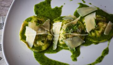 Ravioloni capresi ripieni di mozzarella e pomodoro serviti con crema di basilico e scaglie di parmigiano.