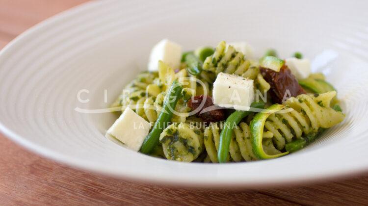 Fusilloni al pesto di basilico e pinoli con fagiolini, zucchine croccanti, pomodori secchi e mozzarella.